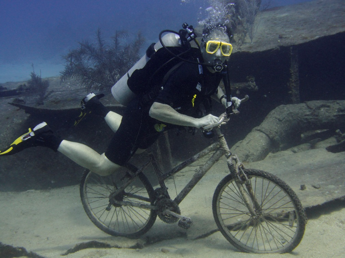 Jim in full scuba gear riding a bicycle underwater