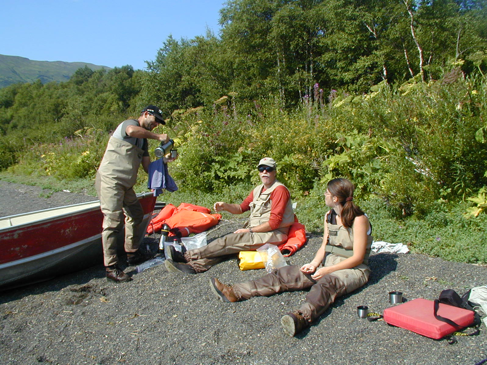 Allan Hicks serving tea to Ray Hilborn and Anne Hilborn on the shores of Little Togiak Lake, Alaska.