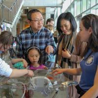 A family looks at a table exhibit during the UW Aquatic Science Open House