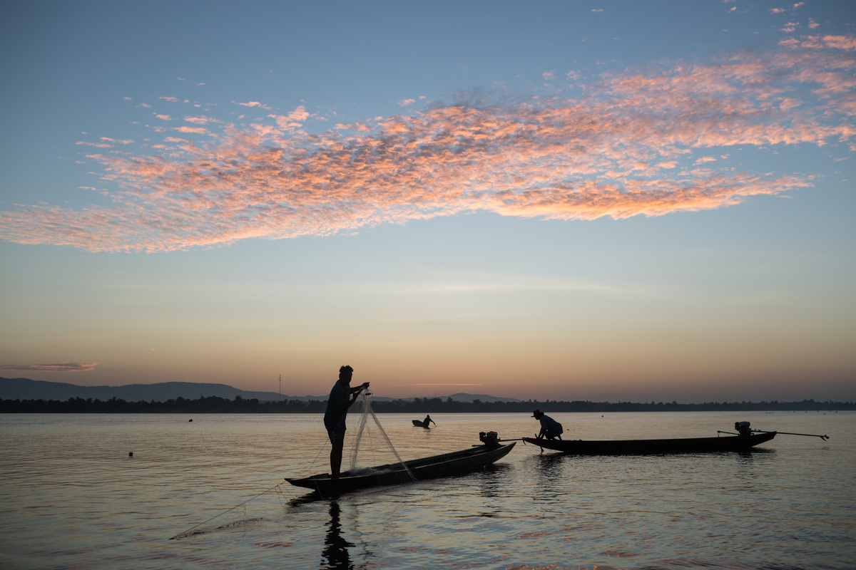 A man standing on a canoe on the Mekong river in Laos