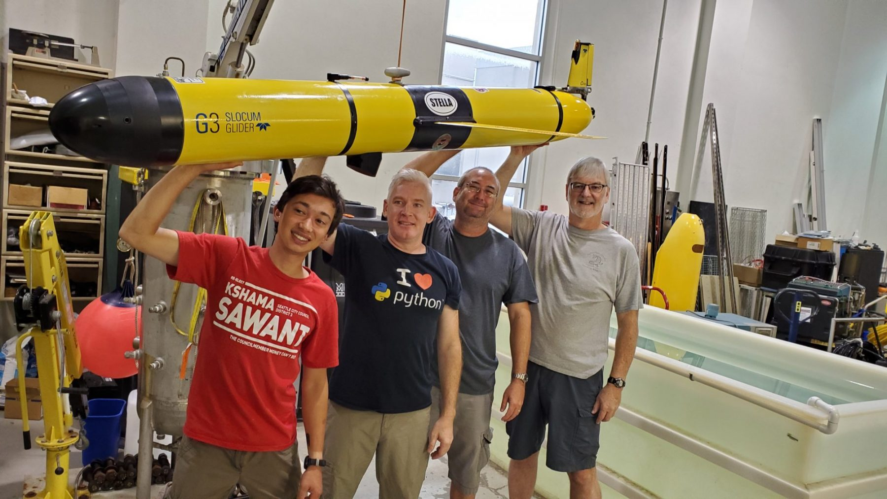 Four of the scientists holding the glider in the lab