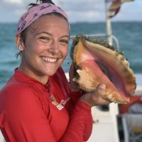 Student hold a queen conch on a boat