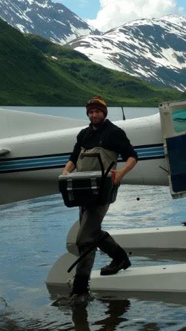 Lukas loading gear off a plane in Alaska