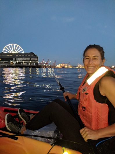 Kerry kayaking along Seattle's seawall at night. The Seattle Great Wheel in the background lit up