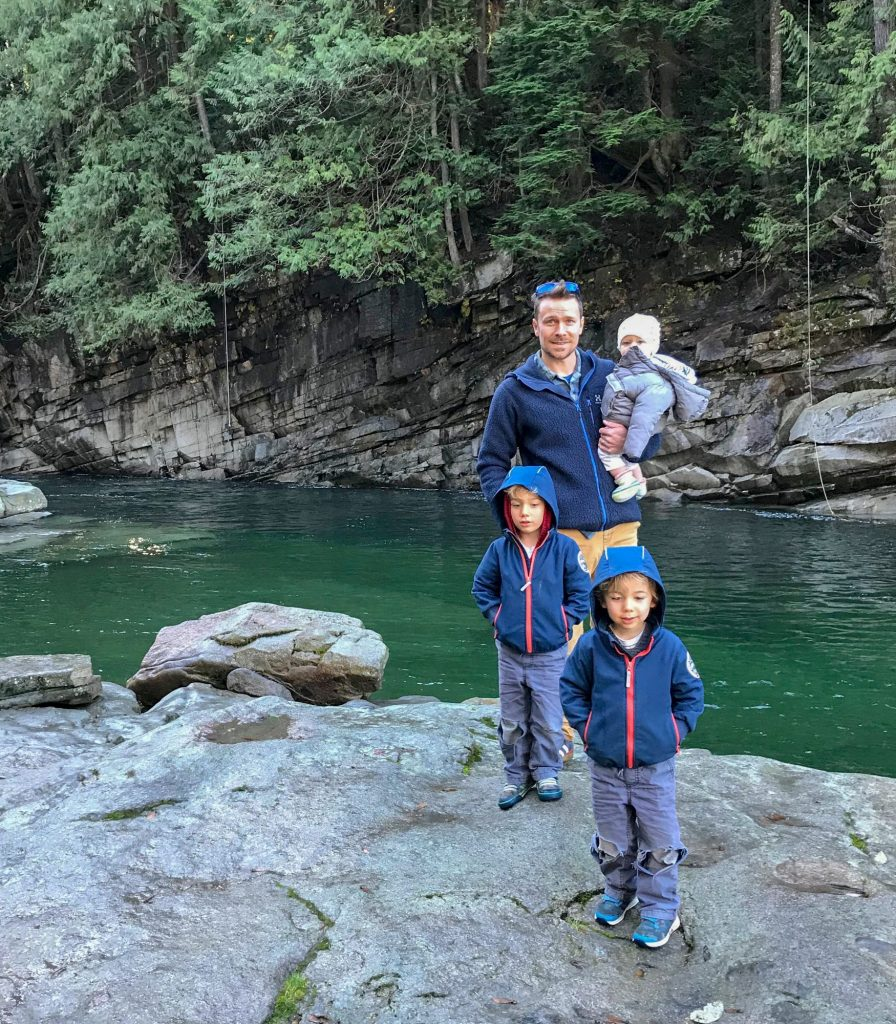 Andrew and his three children on the bank of a river
