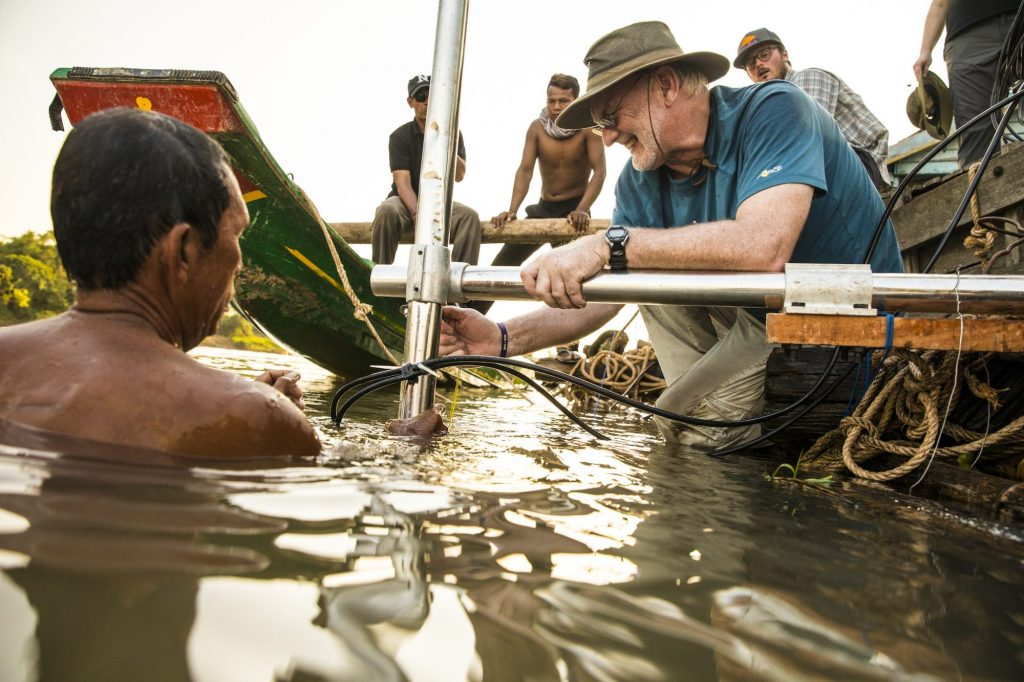 With help from a local fisherman, professor John Horne (right) installs underwater components of an echosounder.