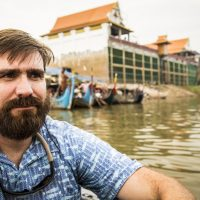 Gordon sitting in a boat along the Mekong River